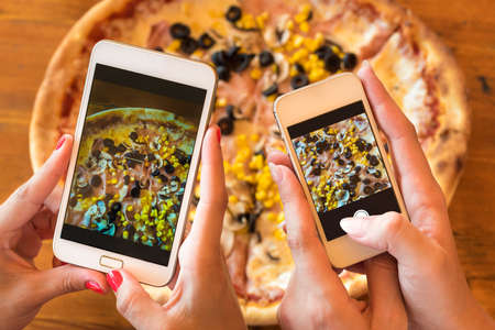 pizza: Female friends using smartphones to take photos of their pizza