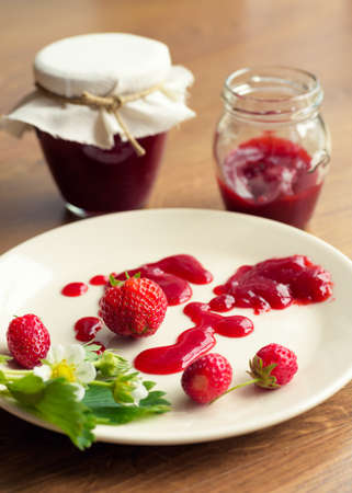 marmelade: Homemade strawberry jam (marmelade) in jars on wooden background. Stock Photo
