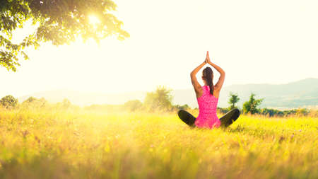 tree position: Young athletic woman practicing yoga on a meadow at sunset, image with lens flare Stock Photo