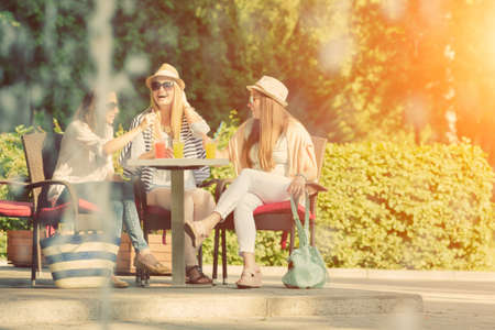 Three attractive girlfriends enjoying cocktails in an outdoor cafe, friendship concept