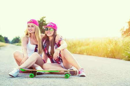 fashion girl: Attractive smiling hipster teenage friends with skateboard, colorised image with sunflare
