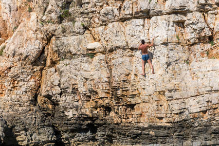 man climbing: Young athletic man climbing sea cliffs without rope or harness in Croatia
