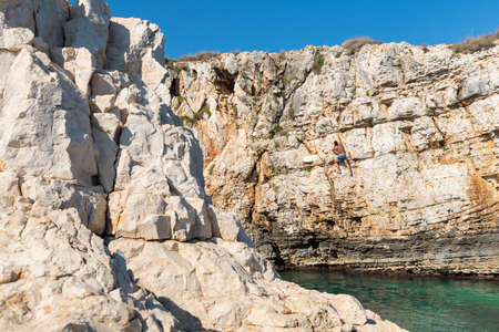 adrenaline rush: Young athletic man climbing sea cliffs without rope or harness in Croatia