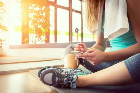 fitness: Attraente donna bionda con il telefono astuto, riposa dopo l'allenamento in palestra Archivio Fotografico