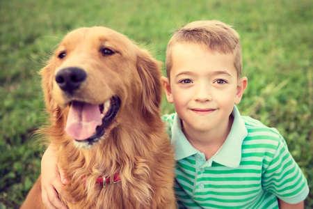 Cute little boy hugging his golden retriever pet dog