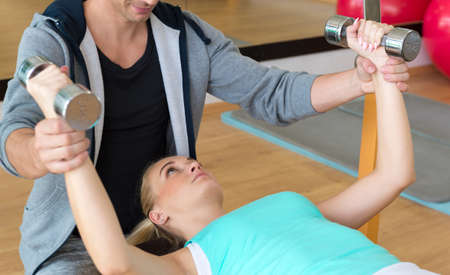 personal trainer: Personal trainer helping woman working with dumbbells