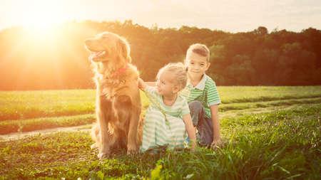 perros jugando: Adorable hermano y hermana jugando con el perro mascota