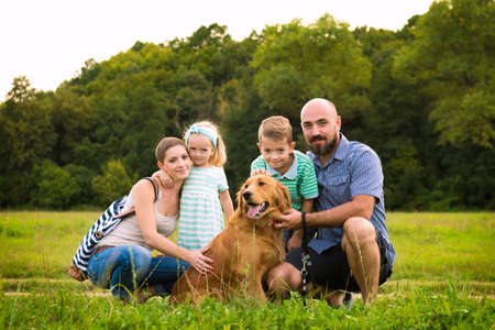 fun day: Beautiful young family with their pet dog, golden retriever