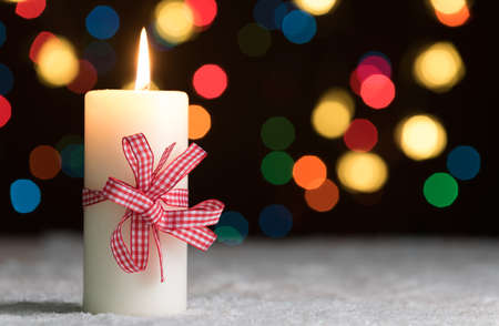 Burning candle with red bow, in snow, with defocussed fairy lights, bokeh in the background, Festive Christmas background with copyspace Standard-Bild