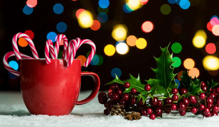 defocussed: Red mug with candy canes in snow with defocussed fairy lights, bokeh in the background, Festive Christmas background