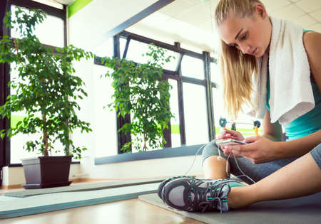 workout: Attractive blond woman with smart phone, resting after gym workout