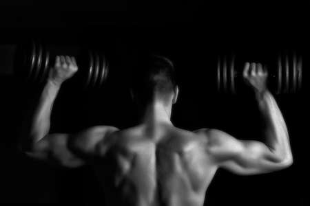 lifting: Handsome young muscular man lifting weights over dark background Stock Photo