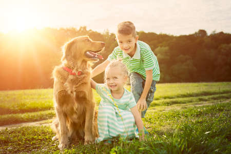Adorable brother and sister playing with pet dog