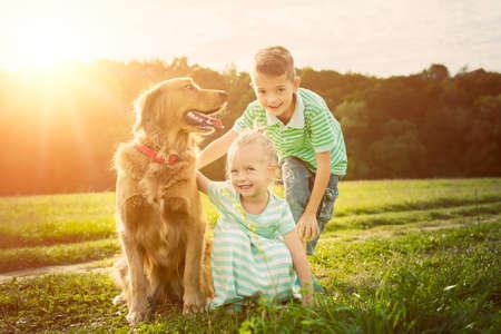 Adorable hermano y hermana jugando con el perro mascota