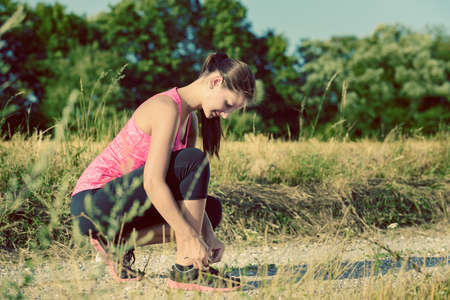 shoe laces: Attractive female runner tying her shoe laces