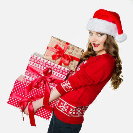 loads: Gorgeous woman holding loads of heavy presents, funny xmas concept