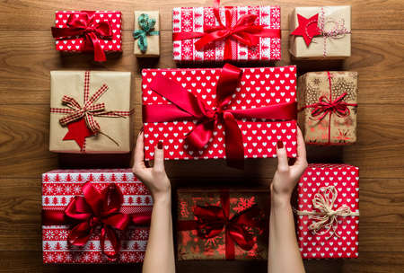 brown paper: Woman organising beautifuly wrapped vintage christmas presents on wooden background, view from above