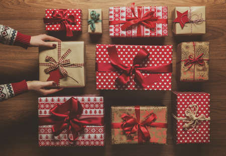 organising: Woman organising beautifuly wrapped vintage christmas presents on wooden background, image with haze, view from above