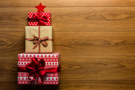christmas tree presents: Christmas tree made of beautifuly wrapped presents on wooden background, view from above