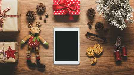 Desk view from above with digital tablet and presents, online shopping retro xmas concept with copy space 스톡 콘텐츠