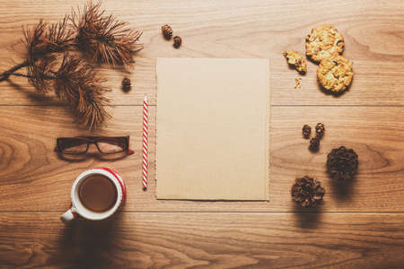 christmas list: Magical christmas theme background, pine cones, coffee, cookies and an empty letter to santa on wooden table Stock Photo