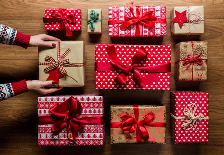 Woman organising beautifuly wrapped vintage christmas presents on wooden background, view from above