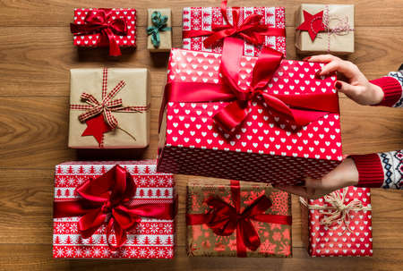 organising: Woman organising beautifuly wrapped vintage christmas presents on wooden background, view from above