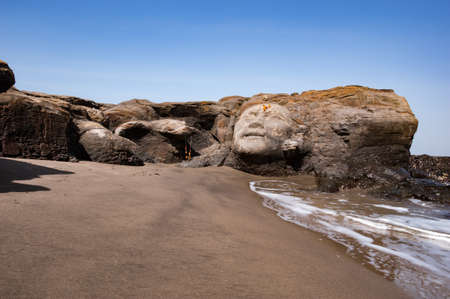 large rock: Vagator Beach in North Goa, face of Shiva carved in to a large rock Stock Photo