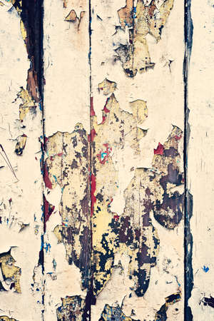 severely: Wooden wall with beige paint, severely weathered and peeling