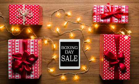 boxing day sale: Desk view from above with digital tablet, presents and christmas lights, retro Boxing Day Sale concept Stock Photo