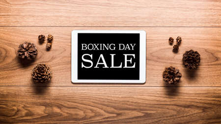 boxing day sale: Magical Boxing Day Sale theme background, pine cones and digital tablet on wooden table Stock Photo