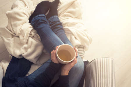 comfy: Young woman at home sitting in comfy armchair and drinking tea, view from above