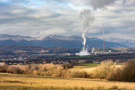 urbanism: Powerplant in Slovakia seen in distance surrounded by nature and small town. Symbol of Technology, pollution and urbanism Stock Photo