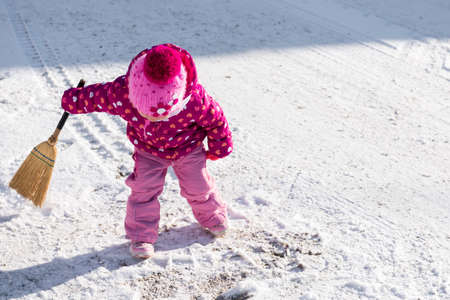 seson: Cute little girl playing with a broom outside during snowy winter day