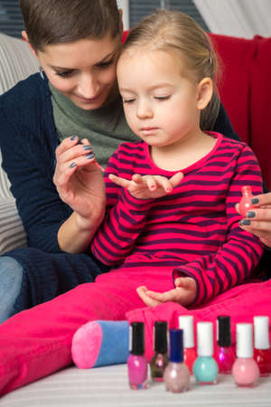 spontaneous painting: Mother and daughter having fun painting fingernails, family time concept