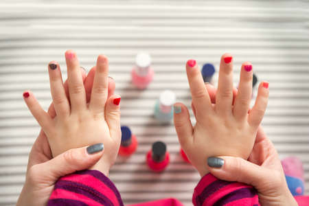 Mother and daughter having fun painting fingernails, family time concept, view from above
