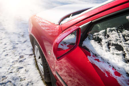 inconvenience: Snow covered red car parked outside, with focus on rear view mirror, winter transport issues