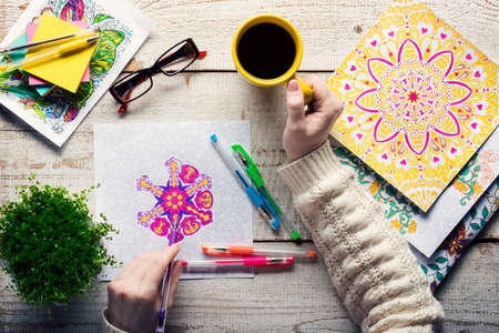 page views: Woman coloring an adult coloring book, new stress relieving trend, mindfulness concept, hand detail