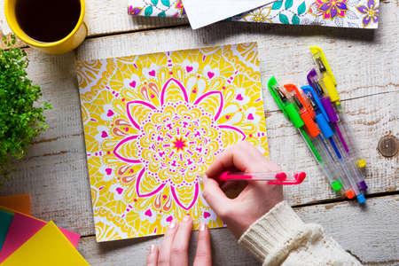 Mujer colorear un libro de colorear para adultos, nueva tendencia para aliviar el estrés, el concepto de la atención plena, detalle mano