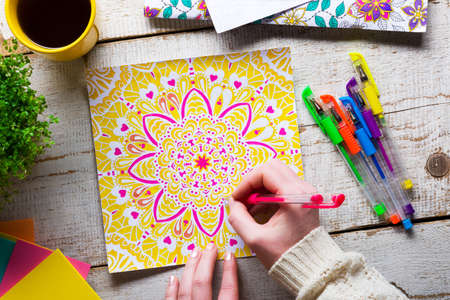 COLOURING: Woman coloring an adult coloring book, new stress relieving trend, mindfulness concept, hand detail