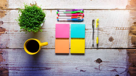 Retro white wooden table with empty colorful sticky notes, different gel pens and cup of coffee