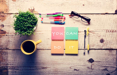 Retro white wooden table with motivational quote on colorful sticky notes, different gel pens and cup of coffee