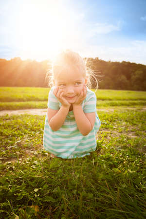 cheeky: Adorable blond little girl with cheeky smile, outdoors play time Stock Photo