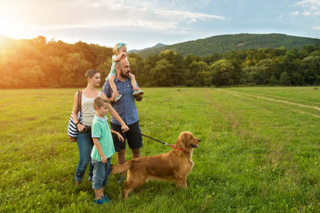 Beautiful young family with their pet dog, golden retriever