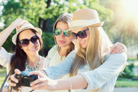 Selfie. Three attractive girls taking picture at summer holidays, girls with camera taking self-portrait on their travel vacation