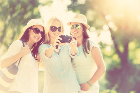 spontaneous expression: Selfie. Three attractive girls taking picture at summer holidays, girls with camera taking self-portrait on their travel vacation