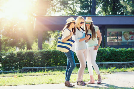 smilie: Three attractive girls looking at photos on their camera at summer holidays, girl friends on their travel vacation