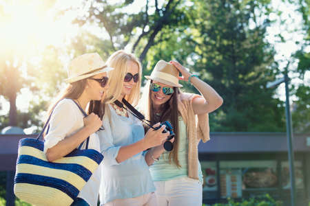 spontaneous expression: Three attractive girls looking at photos on their camera at summer holidays, girl friends on their travel vacation