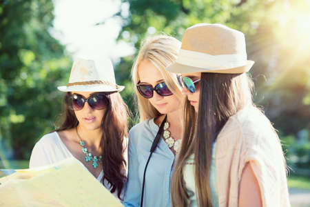 spontaneous expression: Three attractive girls looking for directions on a map at summer holidays, vacation concept