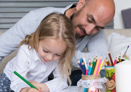 parental love: Father and daughter drawing together, creativity and learning concept Stock Photo